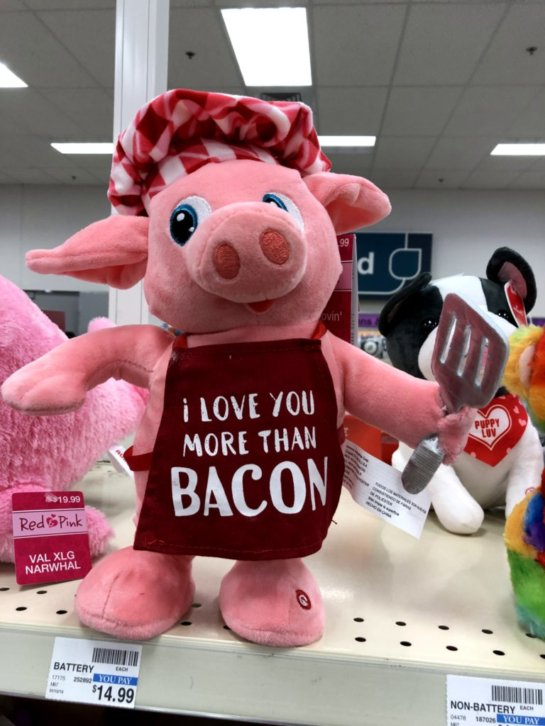 A stuffed animal pig dressed as a cook, wearing an apron that says I love you more than bacon.